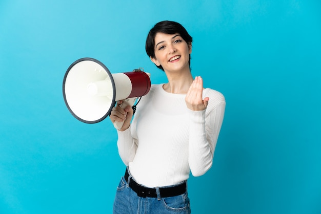 Woman with short hair over isolated wall holding a megaphone and inviting to come with hand
