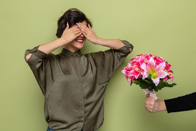 Woman with short hair looking surprised covering eyes with hands while receiving bouquet of flowers from her boyfriend celebrating international women's day march 8 standing over green background
