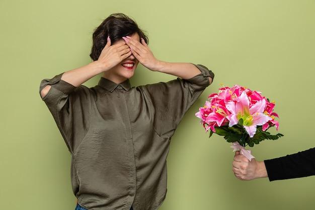 Женщина с короткими волосами выглядит удивленно, прикрывая глаза руками, получая букет цветов от своего парня на праздновании международного женского дня 8 марта, стоя на зеленом фоне
