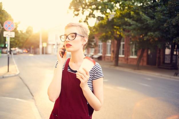 電話で一杯の飲み物を話している通りで短い髪の女性