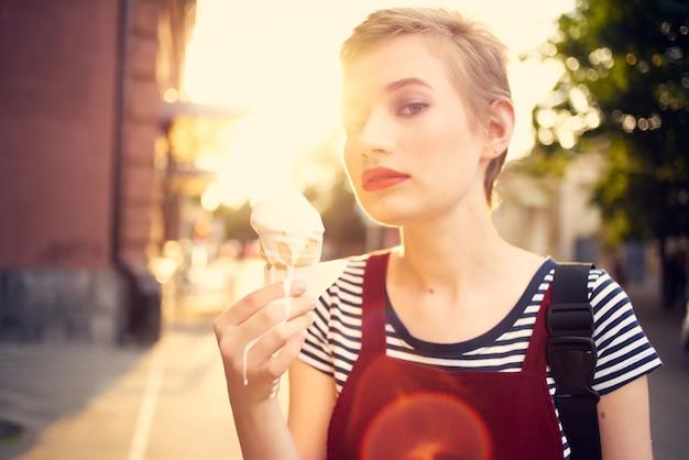 彼女の手でアイスクリームを楽しんで通りで短い髪の女性