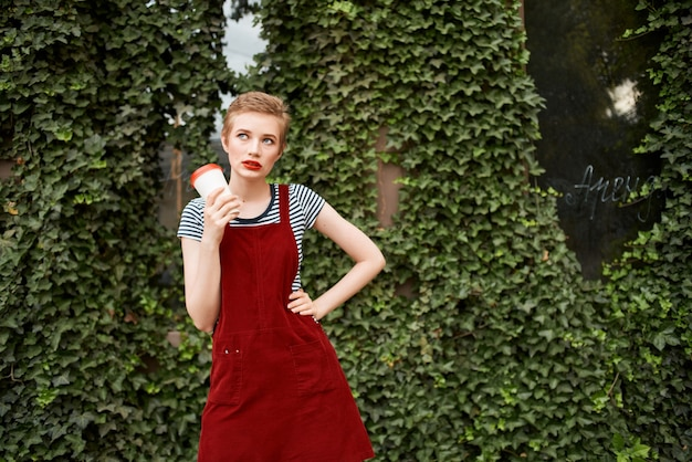 Woman with short hair outdoors in summer cup of coffee