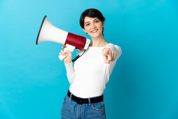 Женщина с короткими волосами держит мегафон и улыбается, указывая вперед