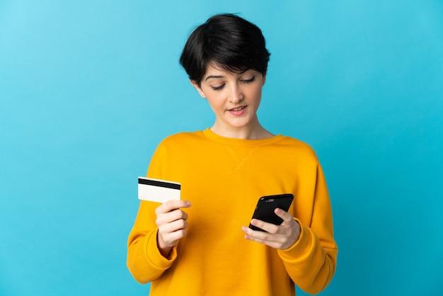Женщина с короткими волосами на изолированном фоне покупает с мобильного телефона с помощью кредитной карты