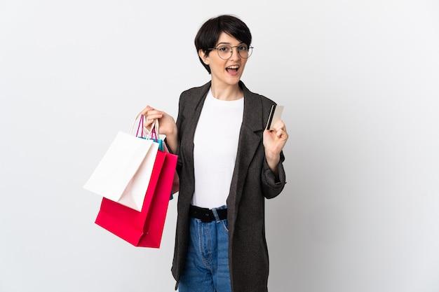 Женщина с короткими волосами на изолированном фоне, держащая хозяйственные сумки и кредитную карту
