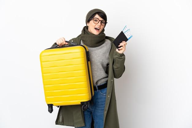 スーツケースとパスポートと休暇で孤立した背景の上の短い髪の女性