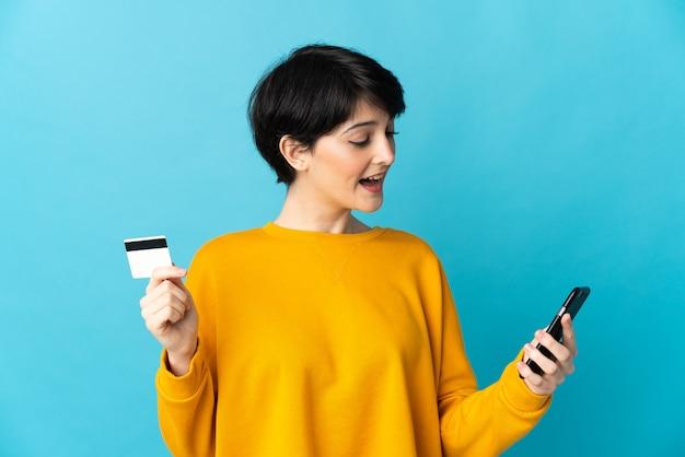 Женщина с короткими волосами над изолированным пространством покупает по мобильному телефону с помощью кредитной карты