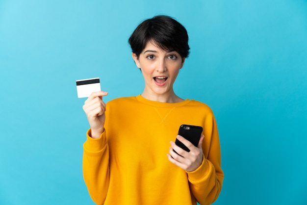 Женщина с короткими волосами над изолированной стеной покупает с помощью мобильного телефона и держит кредитную карту с удивленным выражением лица