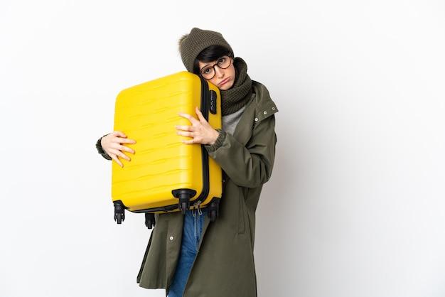 Женщина с короткими волосами над изолированной стеной в отпуске с чемоданом и несчастной