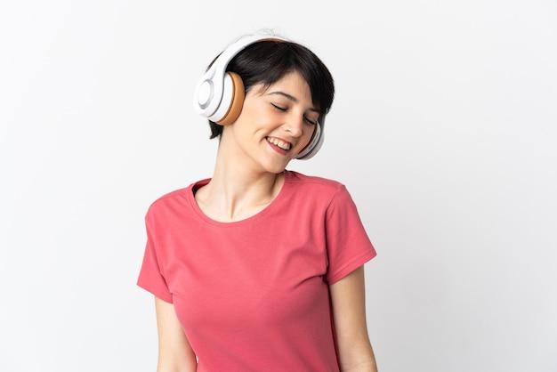 Женщина с короткими волосами над изолированной стеной слушает музыку