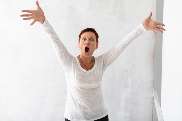 Woman with short hair raising hands
