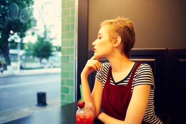 Женщина с короткими волосами, сидя в кафе, коктейль, отдых, образ жизни