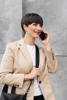 야외에서 전화 통화하는 짧은 머리를 가진 여자