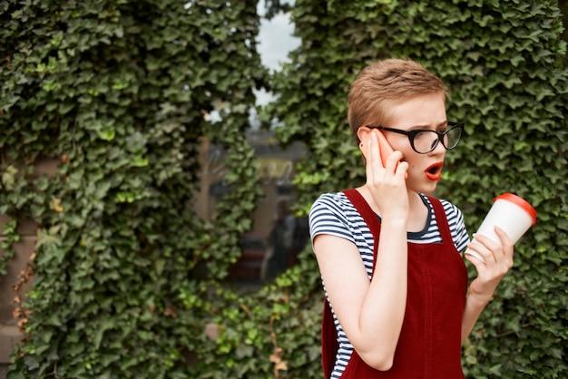 コーヒーの電話カップで話している通りで眼鏡をかけている短い髪の女性。高品質の写真