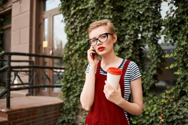 거리에서 전화 통화 하는 안경을 쓰고 짧은 머리를 가진 여자