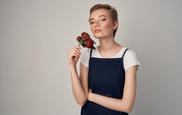 우아한 스타일 화장품의 손에 짧은 머리 꽃을 가진 여자.