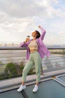 風の強い夏の日に現代の橋の上を歩く短い髪型の女性
