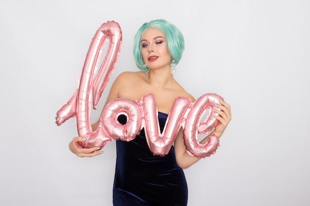Женщина с короткими мятными волосами в темно-синем бархатном платье держит воздушный шар со словом любовь