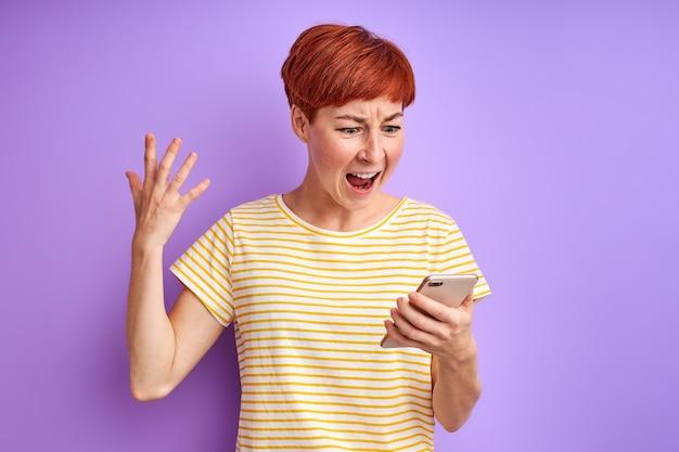 Женщина с короткими рыжими волосами кричит на экране мобильного телефона, споря с кем-то через смартфон онлайн