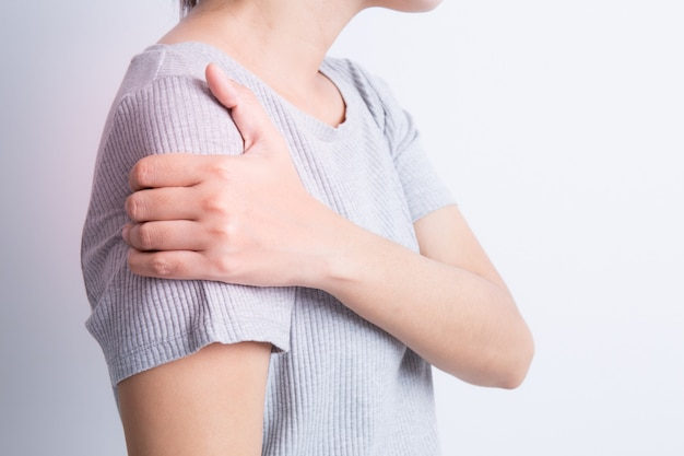 女性の肩の痛み、アジアの女性のシャツグレー