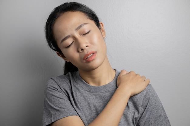 肩の痛みのある女性。肩の痛みを持つ若い女性。女性の肩の痛みに苦しんでいます。