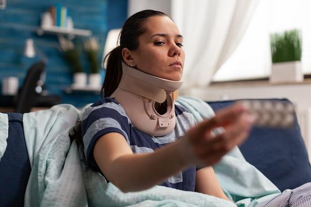 背中と首のパイの治療を受けているソファに病気と頸部フォームの襟を持つ女性...