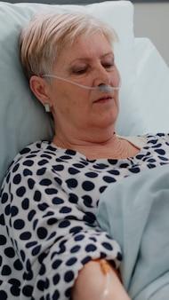 침대에서 치료를 기다리는 질병을 가진 여자