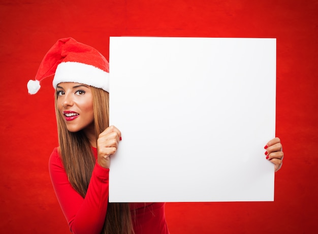 Woman with a sign in a red background