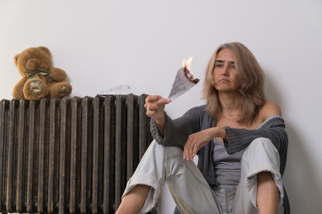 A woman with signs of depression sits on the floor of an apartment next to a battery and holds an airplane set on fire made of paper