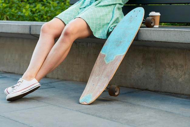 都市のスケートボードを持つ女性