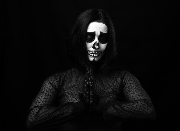 Woman with skeleton make-up stands in prayer pose