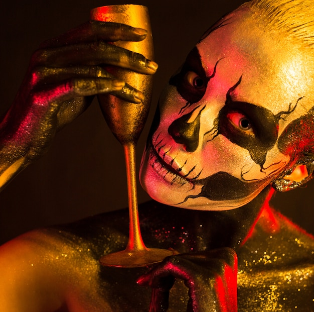 Woman with skeleton makeup holds glass