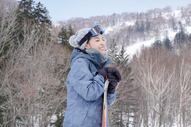 Женщина с лыжами в ее руке носить лыжные очки в снегу зимой горы.