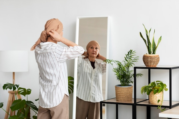 Woman with skin cancer looking in the mirror