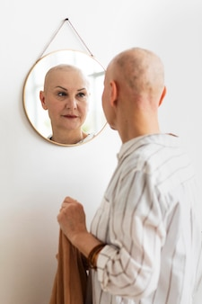 Donna con cancro della pelle che si guarda allo specchio