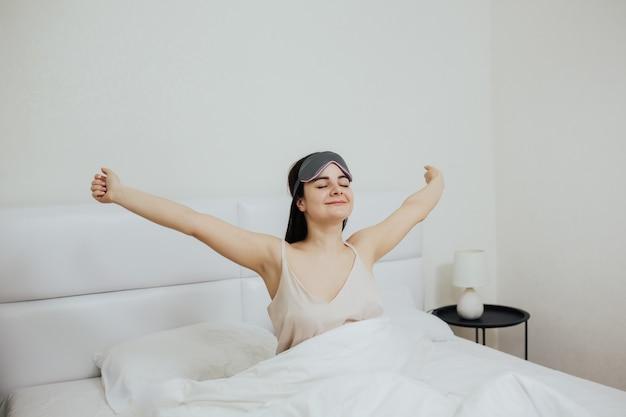 幸せに目を覚まし、腕を伸ばしている睡眠マスクを持つ女性