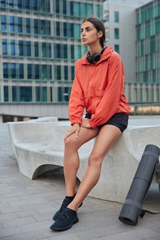 Woman with slender legs being in good physical shape takes break after pilates exercises sits in urbanity place had early morning run admires beautiful city views