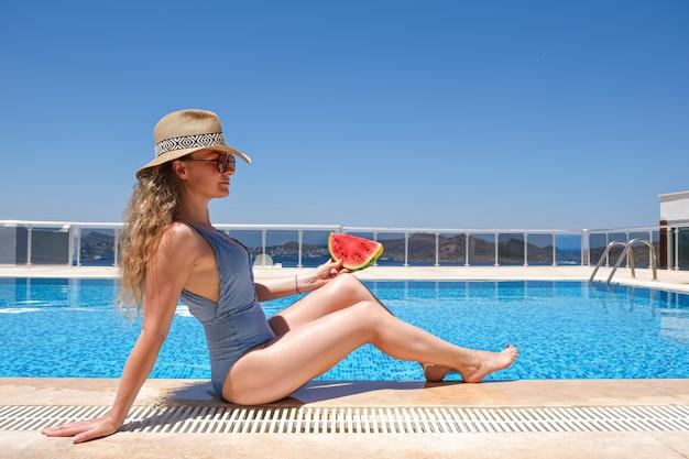 Женщина с ломтиком арбуза в соломенной шляпе загорает, сидя на краю бассейна