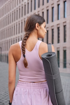 Woman with slim body dressed in sportsclothes has combed pigtail carries rolled up karemat going to have yoga practice walks in downtown outdoor