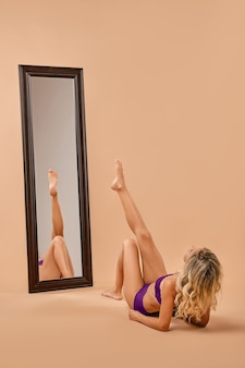 Woman with slim body stands in front of the mirror