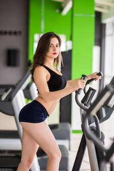 Woman with slim fitness body works on elliptical trainer alone in sportclub