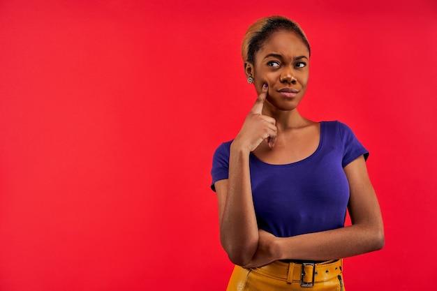 青いtシャツのイヤリングでずるい表情の女性は指で触れる顔を瞑想します