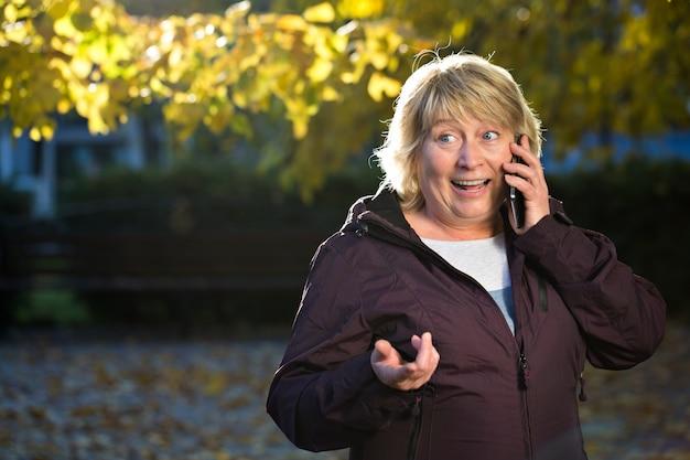 秋の屋外のスマートフォンを持つ女性
