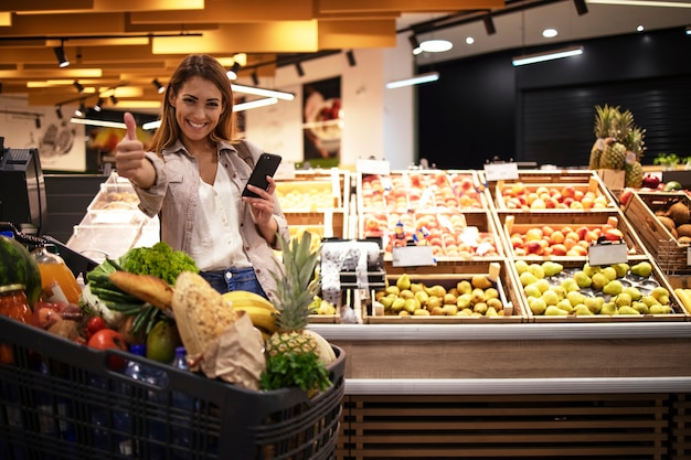Woman with smart phone in supermarket standing by the shelves full of fruit at grocery store holding thumbs up