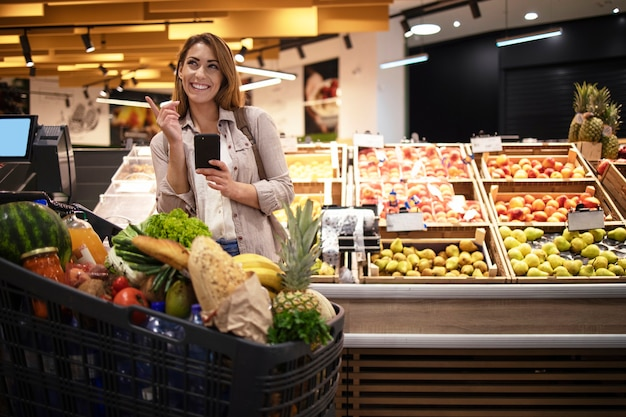 Woman with smart phone in supermarket standing by the shelves full of fruit at grocery store