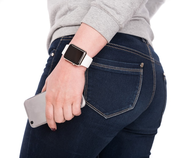 흰색 바탕에 스마트 시계와 스마트폰을 가진 여자.