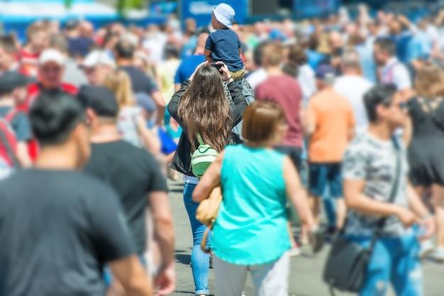 도시 거리를 걷는 사람들의 군중 속에서 스마트폰과 아이를 가진 여자