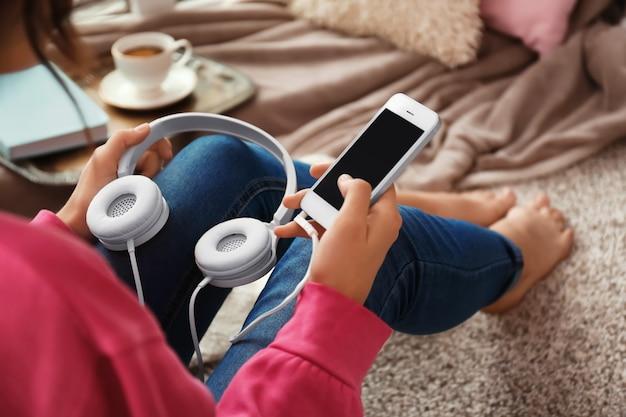 Женщина со смартфоном и наушниками, сидя на полу дома