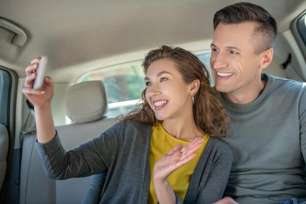 Женщина с смартфон и мужчина в машине