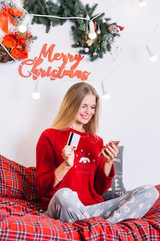 Woman with smartphone and plastic card on bed